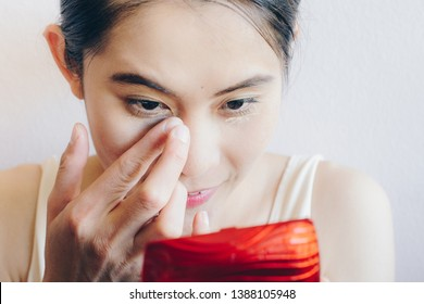 Close up shot of Asian woman face marking and applying cream concealer on her under eyes. Concealer is a type of cosmetic that is used to mask dark circles, age spots, large pores etc.