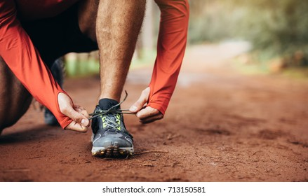 Close up shot of an athlete tying his shoe laces. Man tightening his shoe laces resting on one knee on a mud track.