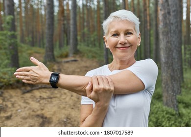 Close up shot of attractive short haired retired female wearing whit t-shirt and smart watch on her wrist to track progress during running, stretching arm, preparing body for cardio exercise