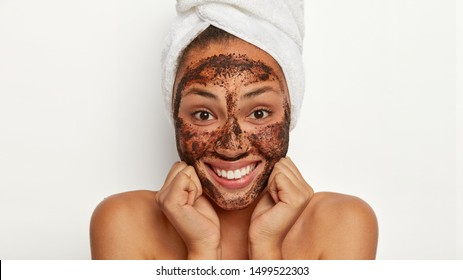 Close up shot of attractive woman keeps hands under chin, exfoliates skin with coffee scrub, smiles gently, wears soft towel, stands topless, isolated over white background. Facial cleansing concept