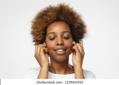 Close up shot of attractive young african american woman in white t shirt listening her favourite song or cool track, feeling the rhythm and vibes with eyes closed