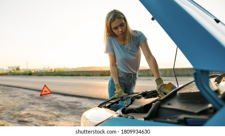 Close up shot of attractive young woman looking under the hood of her broken car, trying to repair it on her own while standing alone after car breakdown on the road side, Web Banner