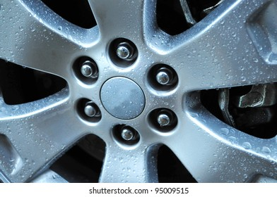 Close up shot of an auto wheel with water drops on its surface
