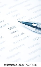 Close up shot of a ball pen on paper with printed business-theme words.