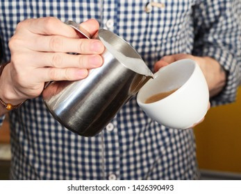 Close up shot of barista in white blue checkered shirt hands making latte art at the freshly brewed cappuccino in big white ceramic mug pouring milk from stainless steel milk frothing pitcher in cozy