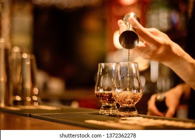 Close up shot of a bartender pouring whisky in a Glencairn glass.