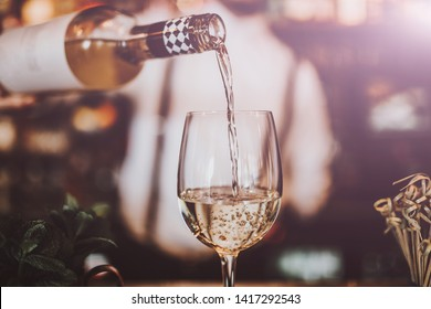 Close up shot of a bartender pouring white wine into a glass. Hospitality, beverage and wine concept.