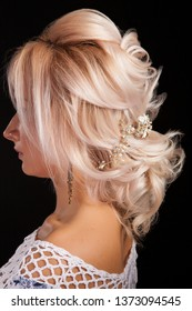 Close up shot of beautiful coiffure on a blonde woman isolated on black background. Long hair.