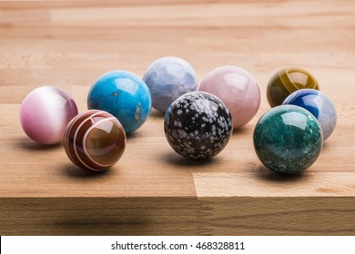 Close up shot of Beautiful Gemstone Spheres & crystal Balls in different varieties on the wooden table