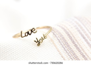 Close up shot of beautiful gold ring with the word love you background for wedding event