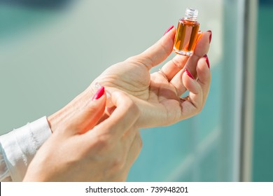 Close Up Shot Of Beautiful Hands Of A Woman Testing Arabic Aromatic Perfume Oud Oil On Her Wrist And Holding The Jar Bottle On Other Hand