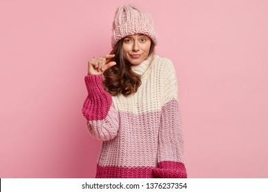 Close up shot of beautiful lady forms something tiny, makes hand gesture, has displeased facial expression, wears fashionable winter clothes, poses against pink background. Very little or small