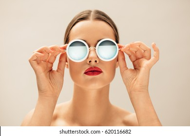 Close up shot of beautiful woman in sunglasses and red lips against beige background. Caucasian female model with glasses.