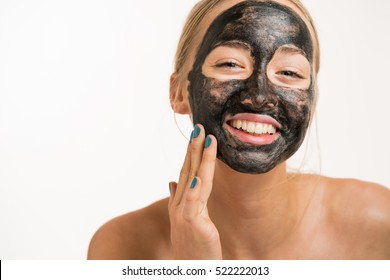 Close up shot of a beauty young woman using a black face mask