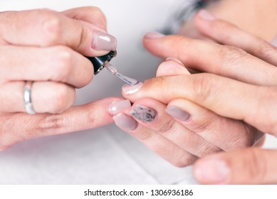 Close up shot of a beutician applying nail polish to female nail at nail salon .