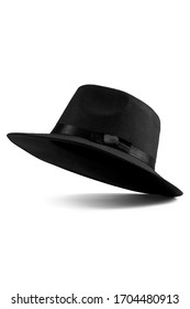 Close up shot of a black fedora hat with the black silk ribbon and a bow around a crown. The classic hat is isolated on the white backdrop.
