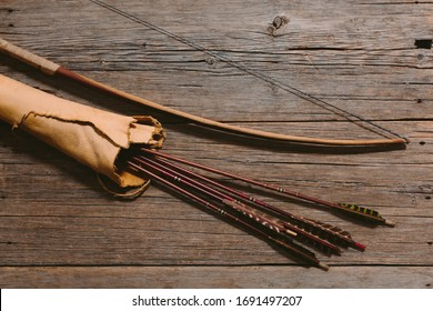 Close up shot of bow laying beside arrows in a leather quiver on wooden planks