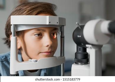 Close up shot of boy checking vision with tonometer at eye clinic
