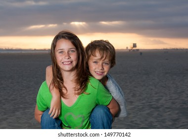 Close up shot of a brother and hugging his sister from behind with a beautiful sunset in the background