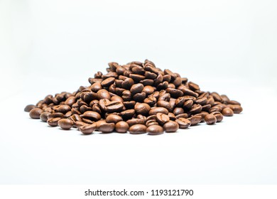 Close up shot of brown roasted coffee beans isolated on white background.