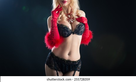 Close up shot of a busty woman in vintage black bra and red boa. Studio shot on black background.