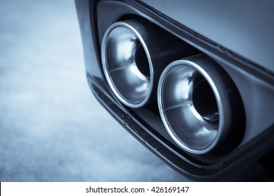 Close up shot of a car's double exhaust pipe.