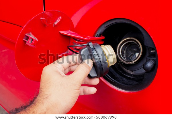Close up shot of a car's. Open fuel tank lid in red car. Refueling a car at a fuel station.