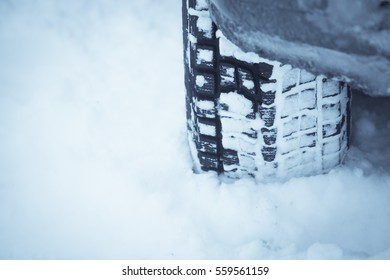 Close up shot of a car's winter tire, in snow.