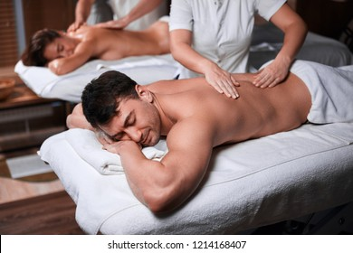 Close up shot of a caucasian young couple lying with his eyes closed receiving relaxing head massage at the spa salon. relaxation rejuvenation relief and wellness concept. Focus on man.