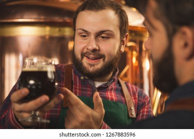 Close up shot of a cheerful bearded brewer smiling, talking to colleague, examining dark beer in a glass. Two brewers producing craft beer at their microbrewery. Manufacturing, small business concept