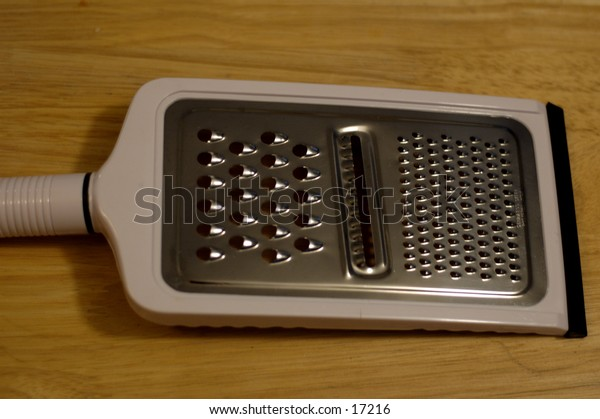A close up shot of a cheese grater against a wooden table