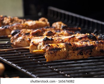 Close shot of chicken kebabs cooking on a barbecue.