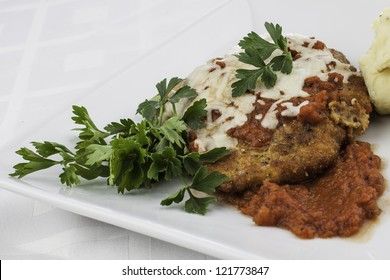 Close up shot of chicken parmesan with parsley garnish