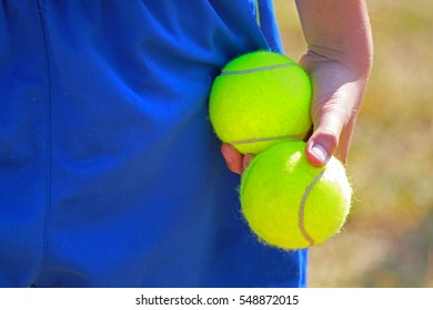 close up shot of a children hand holding two tennis balls