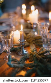 Close up shot of christmas table setting with stylish festive decoration. Traditional family christmas meal in the evening in the light of burning candles.