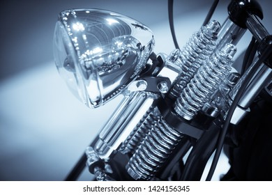 Close up shot of a classic motorcycle chrome headlight and front suspension.