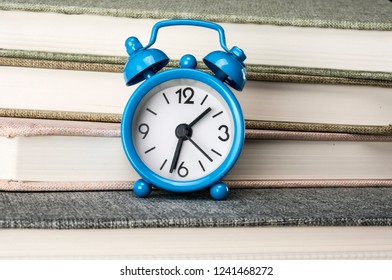 Close up shot of clock and books in the background