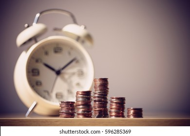 Close up shot of clock and coins with blank background. Business Finance and Money concept,Time is money. Vintage process style.