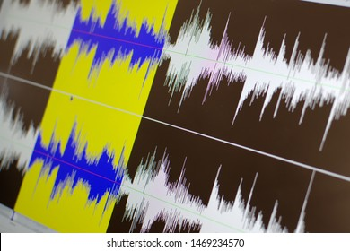 Close up shot of a computer screen showing a waveform sound visualization in an audio editing software.