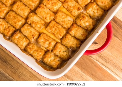 A close up shot of the corner of a pan of freshly baked tater tot hot dish.