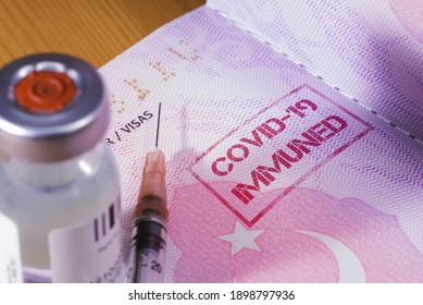 Close up shot of a coronavirus vaccine bottle and a syringe with a Turkeys passport as a vaccine passport Covid 19 Immune text written on the page.