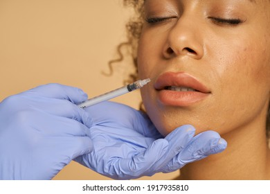 Close up shot of cosmetic injection to the lips of pretty young woman isolated over beige background
