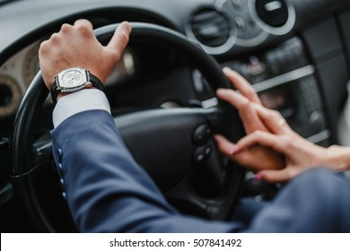 Close up shot of couple traveling by car and holding hands. Focus on hands of man in luxury car interior
