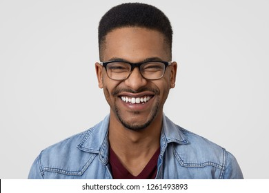 Close up shot of dark skinned guy with broad toothy smile, white teeth, wears denim shirt, spectacles, has short curly hair, laughs at funny joke, expresses happiness, models in studio alone