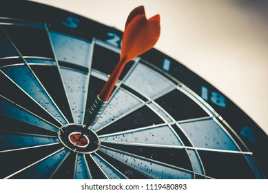 Close up shot of the dart arrow hit on bull eyes of dartboard to represent that the business reached the target of company with dark tone picture style. Target and goal as concept.