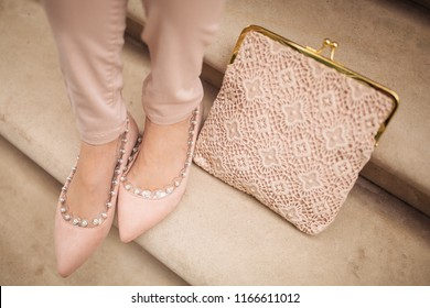 A close up shot of details of the outfit. Young girl sitting on stairs with a pink clutch bag, wearing pink trousers and pink shoes. Blogger, fashion and style concept. Selective focus on the details