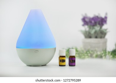 Close up shot of diffuser for living room aromatic essential oils with blue light inside, isolated with blur background.