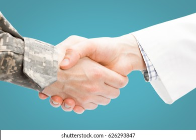 Close up shot of a doctor and a military man shaking hands on light blue background