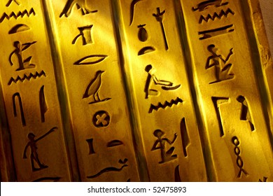 Close up shot of Egyptian hieroglyphics carved into stone with shaft of light