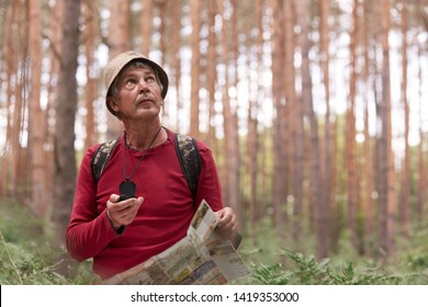 Close up shot of eldery man hiking and looking up at sky, using map and compass for direction for trip in forest, traveling around world, having adventure in wood, enjoying his active vacation.